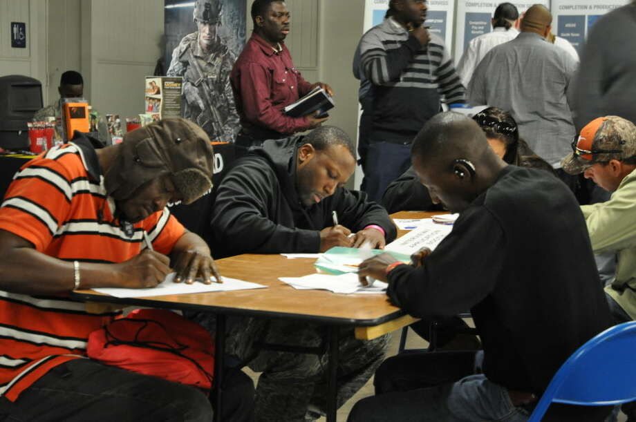 Job seekers fill out applications at an oil-sponsored job fair at the Ector County Coliseum. Photo: Rye Druzin/Reporter-Telegram