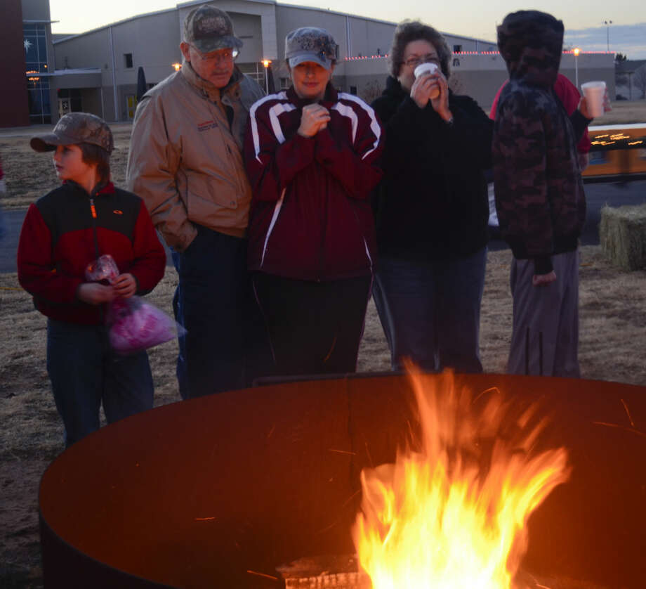 Families huddle around a pit fire to stay warm as they wait to go on a hayride tour of Grasslands light displays Saturday evening at Stonegate Fellowship's Christmastime in the City. Tim Fischer\Reporter-Telegram Photo: Tim Fischer