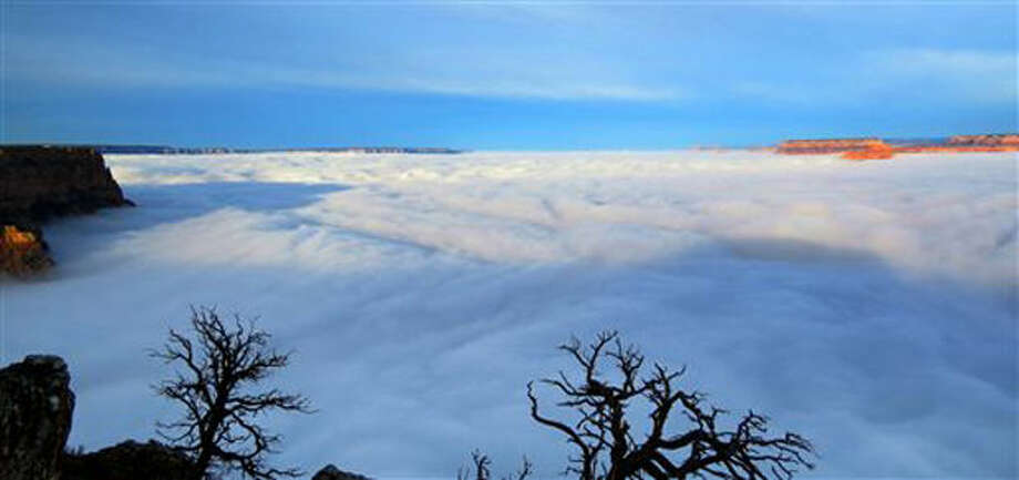 This photo provided by the National Park Service shows dense clouds at the south rim of the Grand Canyon on Thursday, Dec. 11, 2014 in Arizona. A rare weather phenomenon on Thursday had visitors looking out to a sea of thick clouds. The total cloud inversion is expected to hang over the Grand Canyon just below the rim throughout the day. (AP Photo/National Park Service, Maci MacPherson) ----- Photo: Maci MacPherson