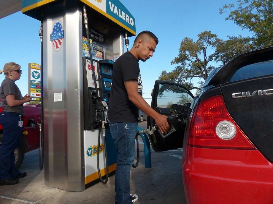 Charles Flores pumps gas at the Valero Station in this Associated Press file photo. Photo: Billy Calzada