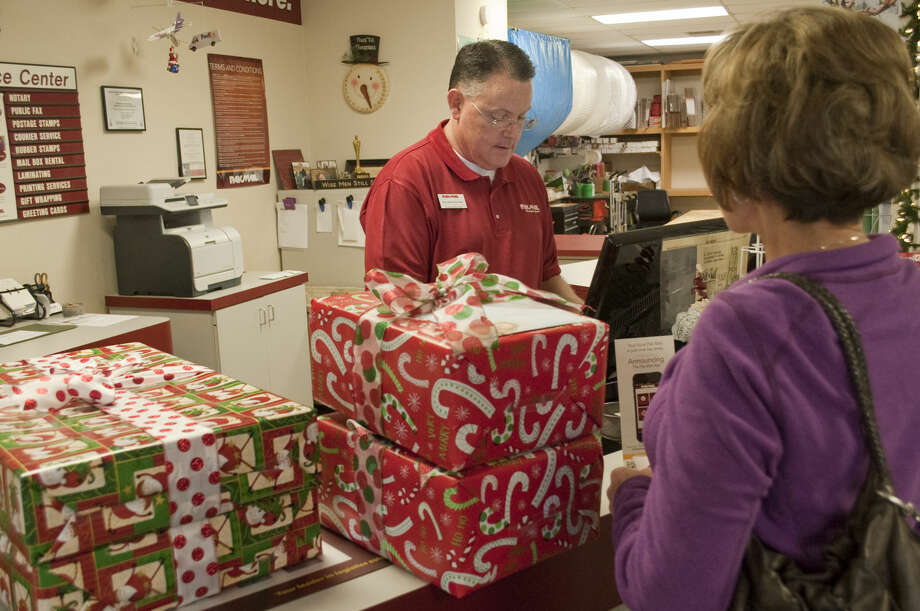 Michelle Standridge brings her Christmas presents to PakMail Thursday to ship out as Gordon Daman enters the addresses into the computer for shipping labels. Tim Fischer\Reporter-Telegram Photo: Tim Fischer