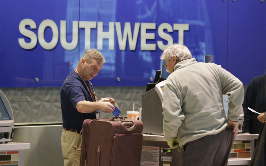 FILE - In this Feb. 3, 2014 file photo, a passenger checks in luggage at the Southwest Airlines counter at Love Field in Dallas. British billionaire Richard Branson on Tuesday, May 6, 2014 said that Virgin American should get gates at Love Field, near downtown Dallas, to create competition for Southwest Airlines, which controls most of the gates there. The U.S. Justice Department agrees. (AP Photo/LM Otero, File) Photo: LM Otero