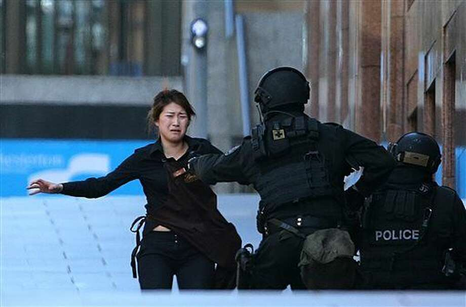 A hostage runs to armed tactical response police officers for safety after she escaped from a cafe under siege at Martin Place in the central business district of Sydney, Australia, Monday, Dec. 15, 2014. New South Wales state police would not say what was happening inside the cafe or whether hostages were being held. But television footage shot through the cafe's windows showed several people with their arms in the air. (AP Photo/Rob Griffith) Photo: Rob Griffith