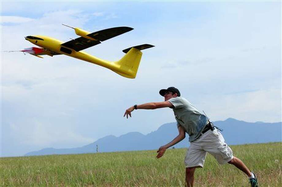 This June 17, 2013 photo, made available courtesy Sean Waugh, NOAA, shows graduate research assistant Kevin Rauhauser, with the University of Colorado's Research and Engineering Center for Unmanned Vehicles, (RECUV), launching the Tempest unmanned aerial vehicle for a test flight on Table Mountain, near Boulder, Colo. Researchers say they've collected promising weather data by flying instrument-laden drones into big storms, and now they want to expand the project in hopes of learning how tornados form.(AP Photo/Sean Waugh, NOAA) Photo: Sean Waugh