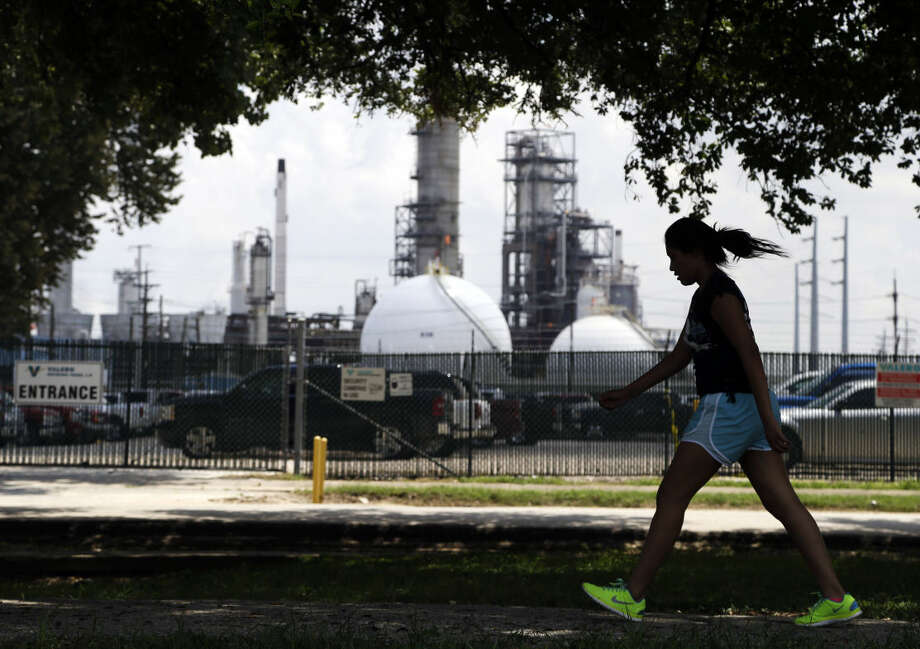 FILE - In this Aug. 4, 2014, file photo a teenage girl walks around the track of a park near the Valero refinery in Houston. How well the oil-rich states survive lower oil prices may hinge on how much they saved during the good times, and how much they depend on oil revenues. Some states, such as Texas, have diversified their economies since oil prices crashed in the mid-1980s. (AP Photo/Pat Sullivan, File) Photo: Pat Sullivan
