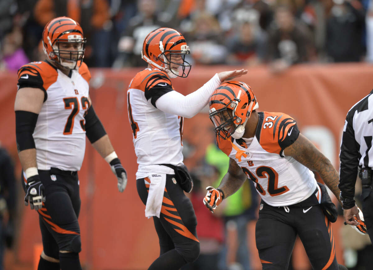 Cincinnati's Eric Winston (73), a Lee grad, walks back to the huddle as running back Jeremy Hill (32) celebrates with quarterback Andy Dalton after Hill's 2-yard touchdown run against the Cleveland Browns in the first quarter of an NFL football game Sunday, Dec. 14, 2014, in Cleveland. (AP Photo/David Richard)