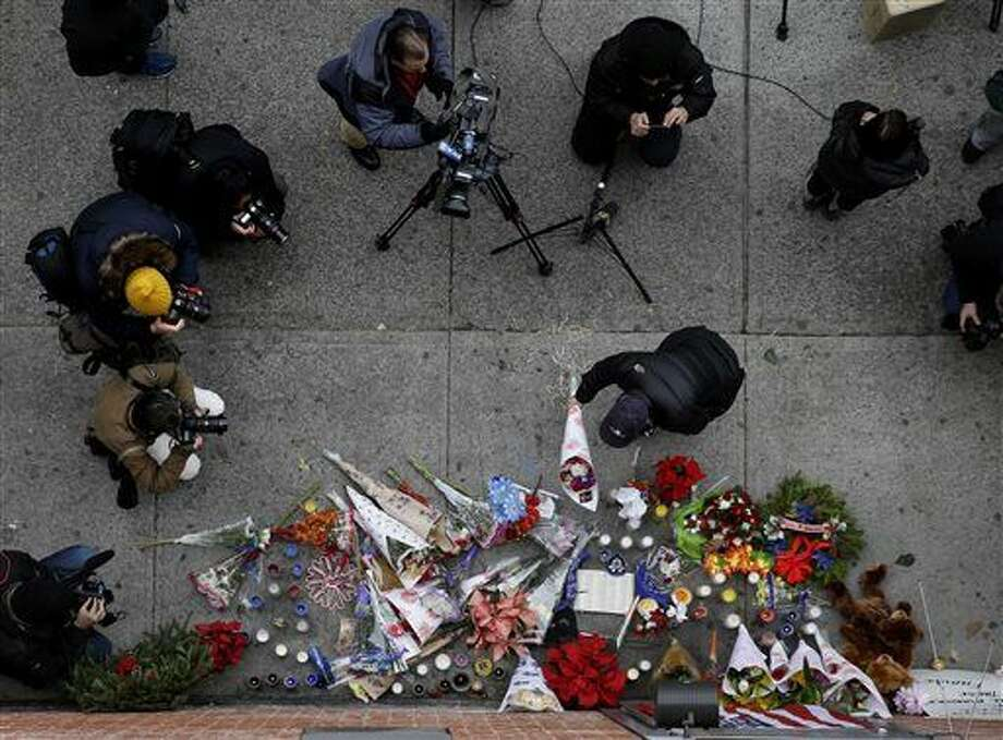 Media surround a man as he leaves flowers at an impromptu memorial near the site where two police officers were killed the day before in the Brooklyn borough of New York, Sunday, Dec. 21, 2014. Just minutes before a wanted poster for Ismaaiyl Brinsley arrived in the NYPD's Real Time Crime Center, he ambushed two officers in their patrol car in broad daylight, fatally shooting them before killing himself inside a subway station. (AP Photo/Seth Wenig) Photo: Seth Wenig