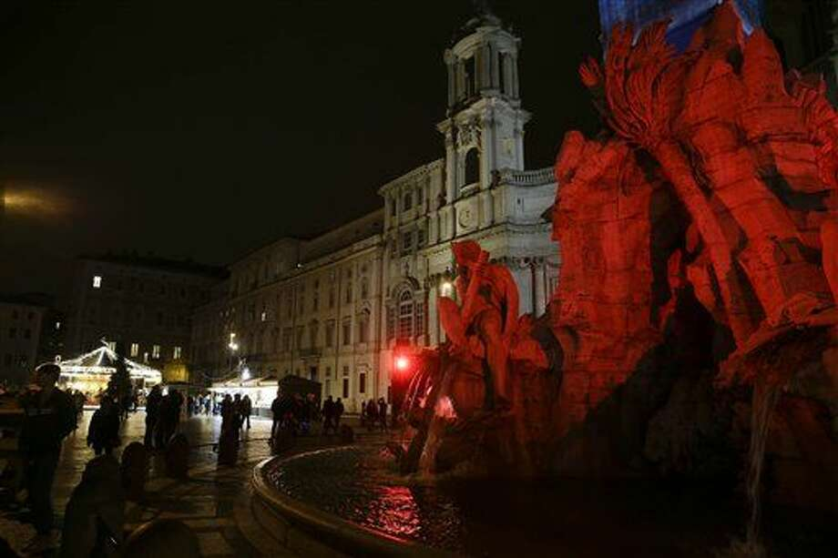 People walk past the Italian sculptor Bernini's Four River fountain, lit up in red, in Piazza Navona, Rome, Tuesday, Dec. 23, 2014. (AP Photo/Gregorio Borgia) Photo: Gregorio Borgia
