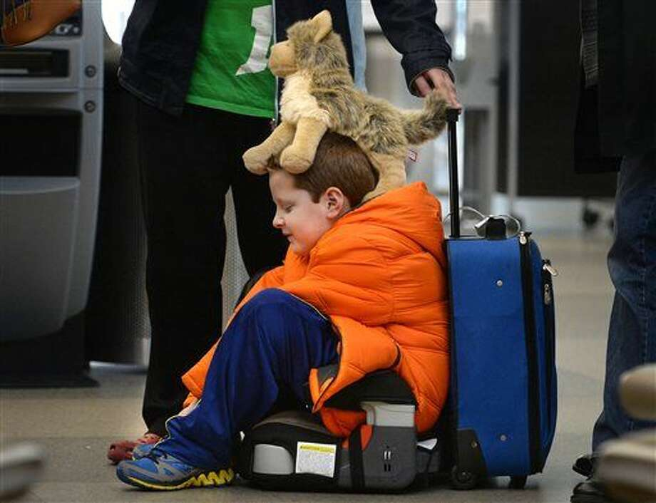 "David Welborn, 7, sits in the lost luggage line at the Delta Airlines desk at RDU International Airport on Tuesday, Dec. 23, 2014. With his trusty dog ""Wolfbaby"" perched on his head, he was with his mother and about 15 other people trying to find their bags after a cross country flight from Washington State. They were headed to Kinston, N.C. for the holidays. (AP Photo/The News & Observer, Chuck Liddy) Photo: Chuck Liddy"