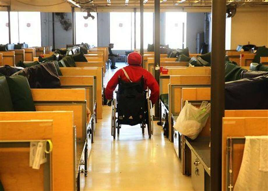 In this Nov. 26, 2014 photo, Chris Easterling rolls past a row of beds inside the Salvation Army shelter where he currently sleeps, in Denver. Easterling came to Denver from Minneapolis in part to use legal marijuana to help ease the pain of his multiple sclerosis. (AP Photo/Brennan Linsley) Photo: Brennan Linsley