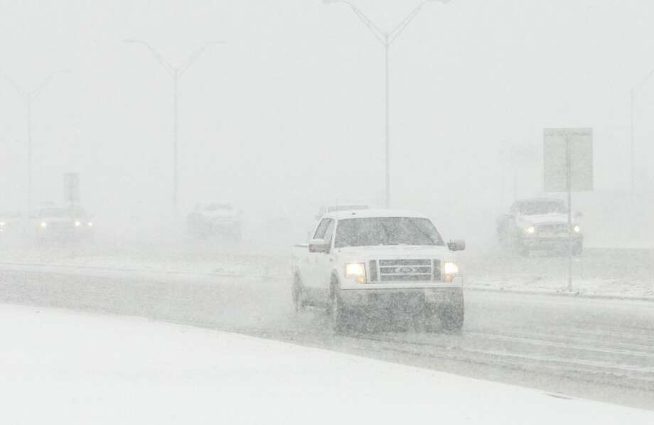 Drivers cautiously drive on West Loop 250 as snow falls in this 2012 file photo. Photo: Midland Reporter-Telegram