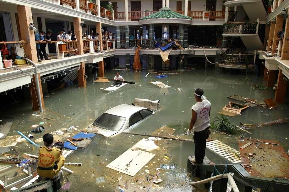 En esta imagen de archivo, tomada el 28 de diciembre de 2004, equipos de rescatistas y de limpieza supervisan la entrada inundada del hotel Seapearl Beach Hotel junto a la playa de Patong, en la isla de Phuket, Tailandia, tras el tsunami que azotó la costa días antes.El viernes se celebra el décimo aniversario de uno de los desastres naturales más letales de la historia: un tsunami, provocado por un gran terremoto fuera de las costas indonesias, que dejó más de 230.000 muertos en 14 países y unos 10.000 millones de dólares en daños. Países desde Indonesia a India o la costa este de África se vieron afectados, dejando impactantes imágenes de muerte y destrucción. (Foto AP/ CP, Deddeda Stemler, archivo) Photo: Deddeda Stemler