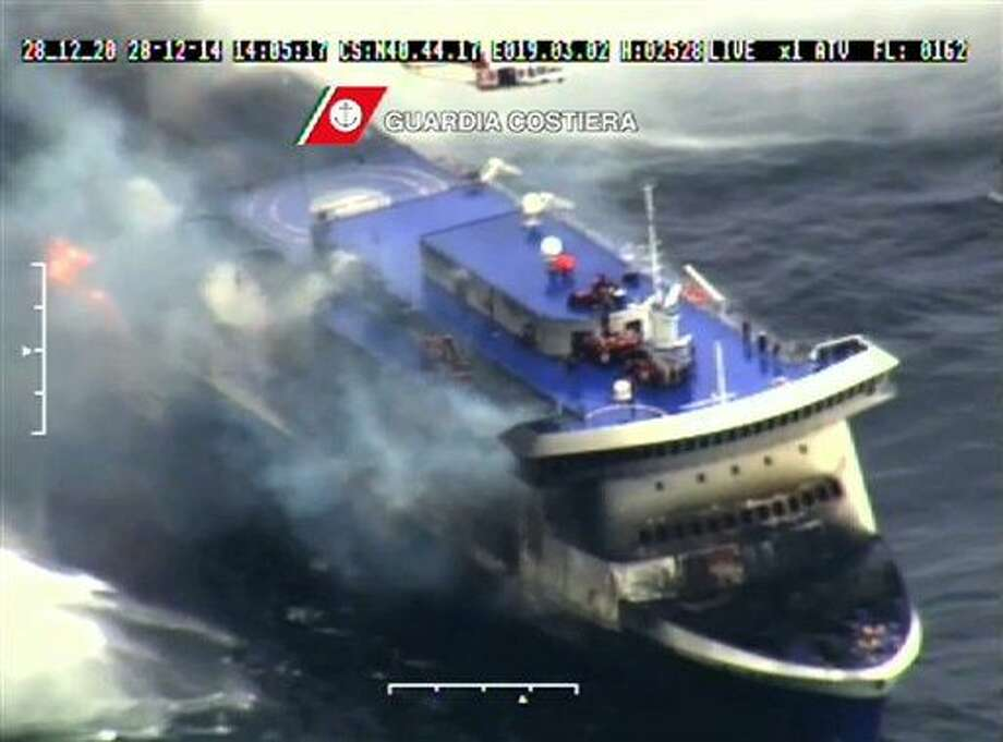 In this image taken from a video released by the Italian Coast Guard, smoke billows from the Italian-flagged Norman Atlantic that caught fire in the Adriatic Sea, Sunday, Dec. 28, 2014. Italian and Greek rescue crews battled gale-force winds and massive waves as they struggled Sunday to evacuate hundreds of people from a ferry on fire and adrift in the channel between Italy and Albania. At least one person died and two were injured. The fire broke out before dawn Sunday on a car deck of the Italian-flagged Norman Atlantic, traveling from the western Greek port of Patras to the Italian port of Ancona on the Adriatic, with 422 passengers and 56 crew members on board. (AP Photo/Italian Coast Guard) Photo: HOPD