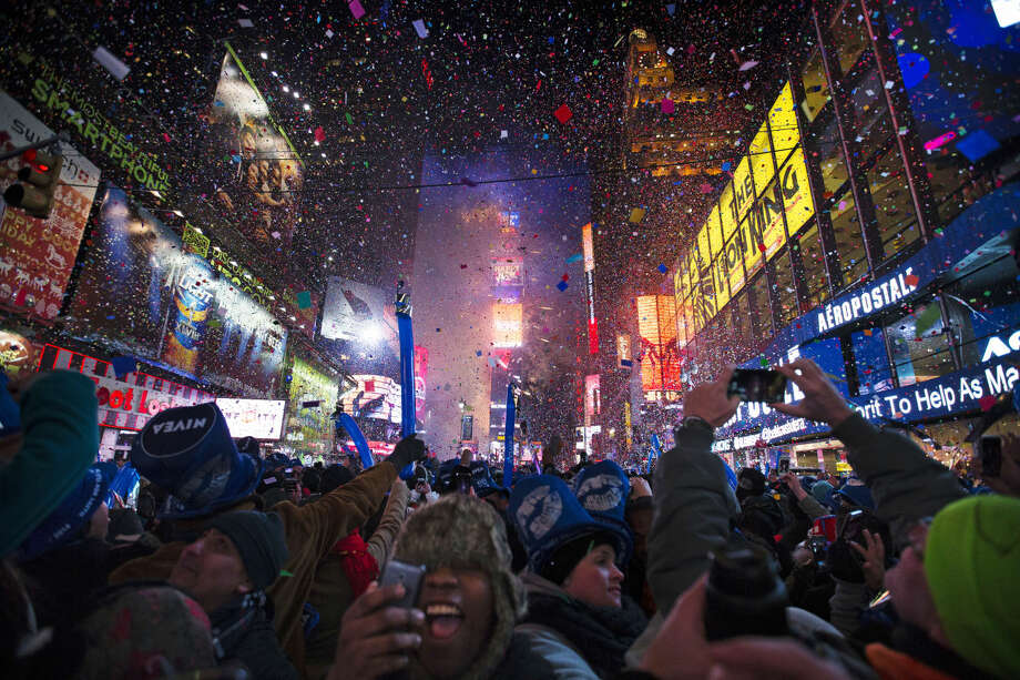FILE - This Jan. 1, 2014, file photo shows revelers cheering under falling confetti at the stroke of midnight during the New Year's Eve celebrations in Times Square, in New York. Americans are closing out 2014 on an optimistic note, according to a new Associated Press-Times Square Alliance poll. Nearly half predict that 2015 will be a better year for them than 2014 was, while only 1 in 10 think it will be worse. There's room for improvement: Americans give the year gone by a resounding 'meh.' (AP Photo/John Minchillo, File) Photo: John Minchillo
