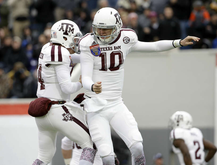 Texas A&M quarterback Kyle Allen (10) celebrates with Conner McQueen (14) after scoring against West Virginia in the first half of the Liberty Bowl NCAA college football game, Monday, Dec. 29, 2014, in Memphis, Tenn. (AP Photo/Mark Humphrey) Photo: Mark Humphrey