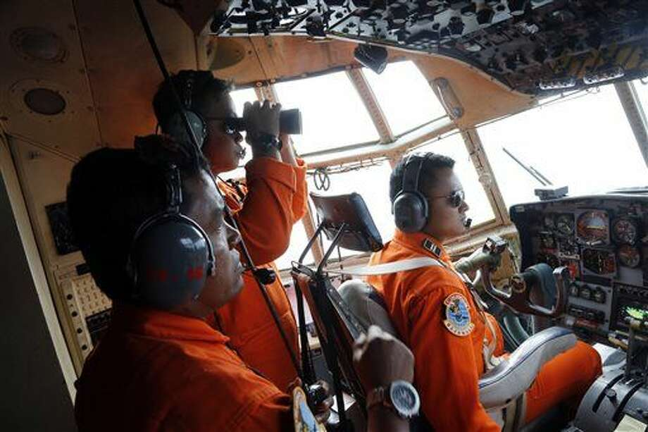 Crew of Indonesian Air Force C-130 airplane of the 31st Air Squadron scan the horizon during a search operation for the missing AirAsia flight 8501 jetliner over the waters of Karimata Strait in Indonesia, Monday, Dec. 29, 2014. Search planes and ships from several countries on Monday were scouring Indonesian waters over which the AirAsia jet disappeared, more than a day into the region's latest aviation mystery. Flight 8501 vanished Sunday in airspace thick with storm clouds on its way from Surabaya, Indonesia, to Singapore. (AP Photo/Dita Alangkara) Photo: Dita Alangkara