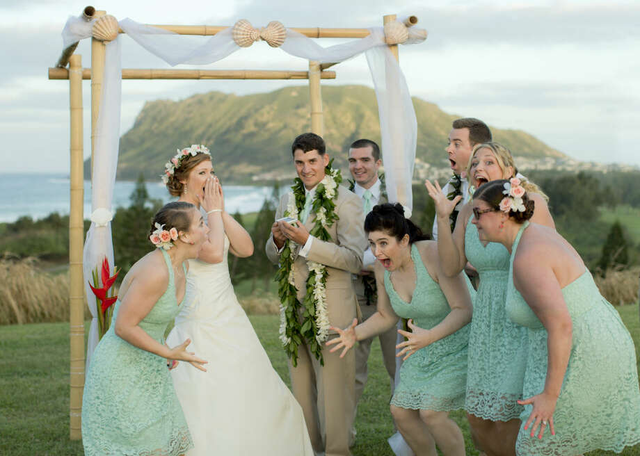 Natalie Heimel, second from left, and Edward Mallue Jr., third from left, and their wedding party react after getting a phone call from President Obama during their ceremony at Kaneohe Klipper Golf Course in Kaneohe Bay, Hawaii. The couple, both U.S. Army captains, had to move their wedding away from the 16th hole because of Obama's golf outing. Obama called the newlyweds to apologize for disrupting their plans and offer his congratulations. Photo: AP/Keao Sunaoka