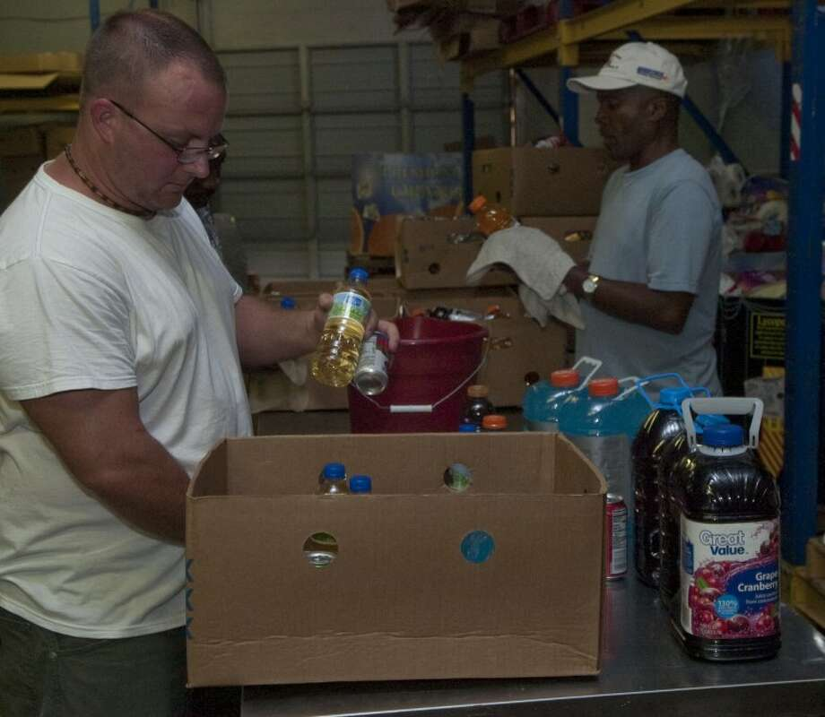 Volunteers Chris Hensen, Deyon Martin, behind and Dennis Joiner wipe off donated drinks before they are repackaged into food boxes Thursday at the West Texas Food Bank in Odessa. Photo: Tim Fischer/Reporter-Telegram