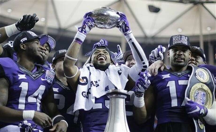 TCU safety Michael Downing holds part of the Peach Bowl trophy after the second half of the Peach Bowl NCAA football game against Mississippi, Wednesday, Dec. 31, 2014, in Atlanta. TCU won 42-3. (AP Photo/David Goldman) Photo: David Goldman