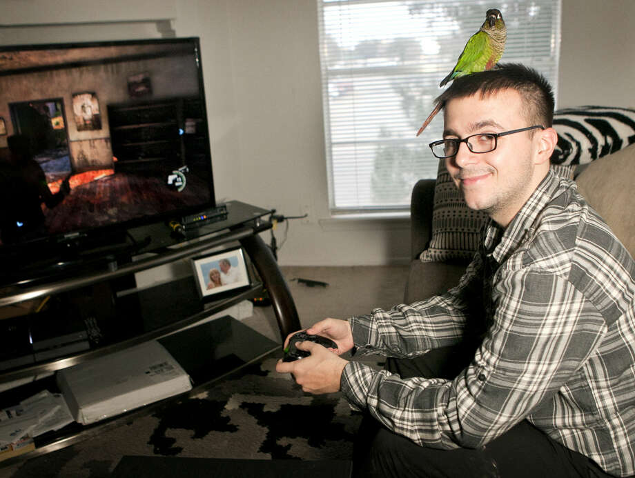 Doug Whitman, a teacher at Barbara Culver Detention Center, plays video games with his pet bird, Caesar, Dec. 10, 2014 at his apartment. James Durbin/Reporter-Telegram Photo: James Durbin