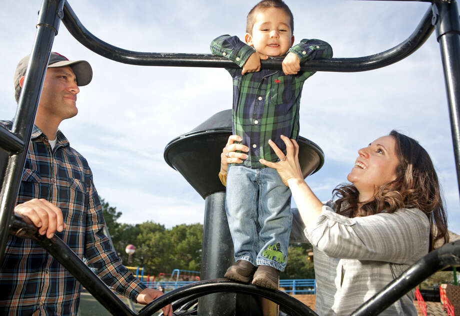 Monica Hernandez, a MISD compliance reporting coordinator, poses for a photo with her family, Rigo and Isaac, age 2, while playing in Opportunity Park, Dec. 13, 2014. James Durbin/Reporter-Telegram Photo: James Durbin