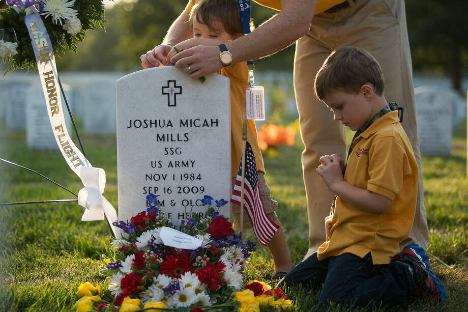 Five-year-old Malachi Mills Thursday kneels next to his fathers grave after the Texas Permian Basin Honor Flight held a wreath laying ceremony in his honer at Arlington National Cemetery. Courtney Sacco|Odessa American Photo: Courtney Sacco