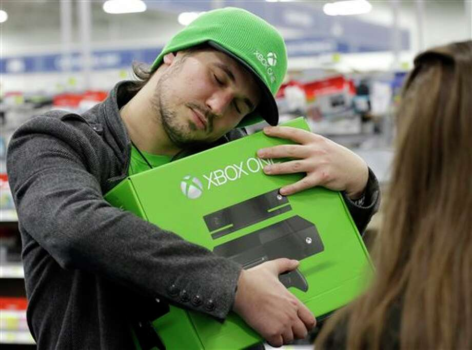 Emanuel Jumatate, from Chicago, hugs his new Xbox One after he purchased it at a Best Buy on Friday, Nov. 22, 2013, in Evanston, Ill. Microsoft is billing the Xbox One, which includes an updated Kinect motion sensor, as an all-in-one entertainment system rather than just a gaming console. (AP Photo/Nam Y. Huh) Photo: Nam Y. Huh / AP2013