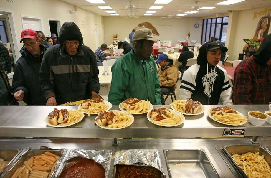 People line up to get their first serving of hotdogs, french-fries and soup as well as enjoy a break from the cold weather Wednesday at Breaking Bread. Cindeka Nealy/Reporter-Telegram Photo: Cindeka Nealy