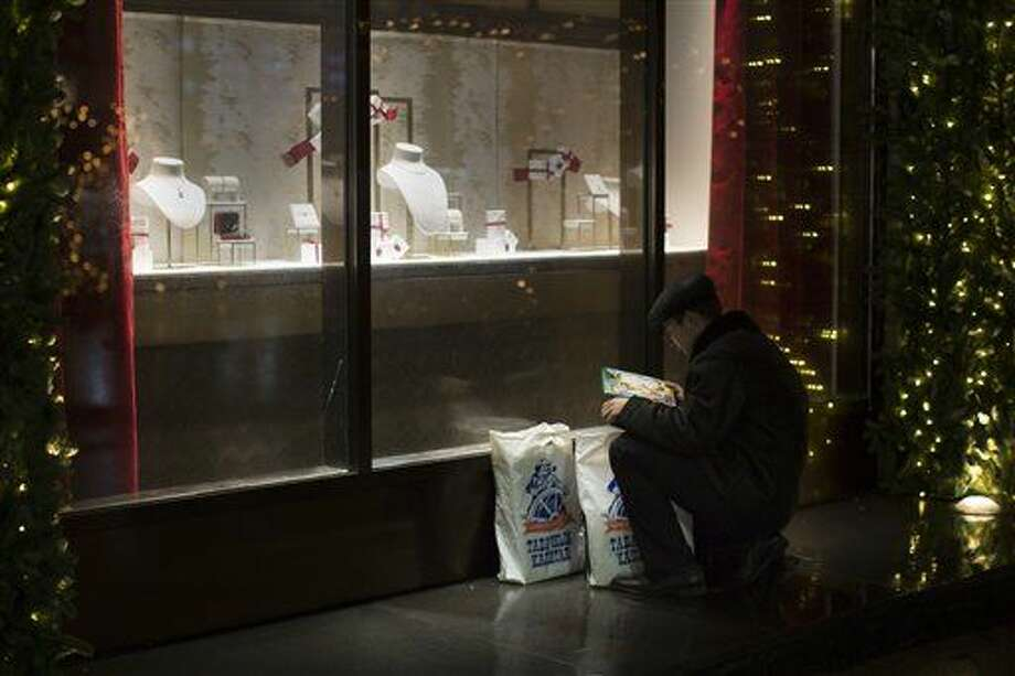 A man studies the contents of his bags in front of a luxury Cartier boutique in Moscow, Russia, Wednesday, Dec. 17, 2014. As the Russian authorities announced a series of measures to ease the pressure on the ruble, which slid 15 percent in the previous two days and raised fears of a bank run, many Russians were buying cars and home appliances — in some cases in record numbers — before prices for these imported goods shoot higher. (AP Photo/Alexander Zemlianichenko) Photo: Alexander Zemlianichenko