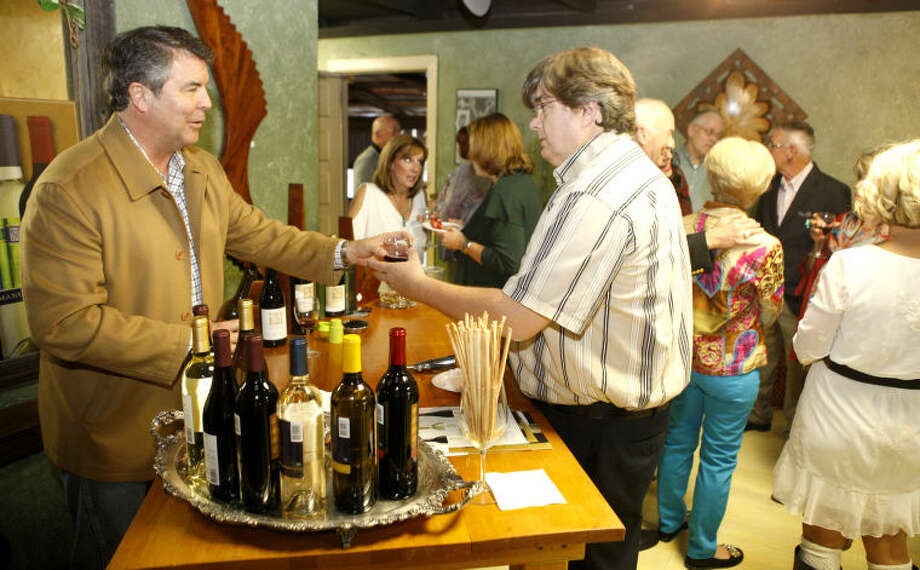Mike Howard of Prairie Creek Beverages hands out a sample of Manuscript wine during an event featuring art by local artist Steve Culver and a wine tasting on Saturday. James Durbin/Reporter-Telegram Photo: JAMES DURBIN