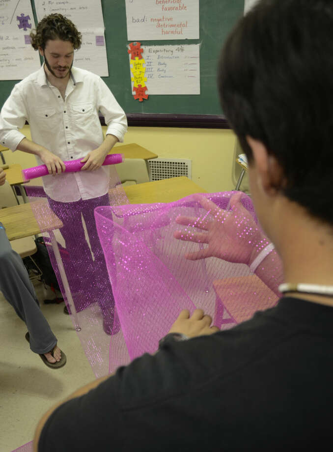 Chandler Hyatt, facing, gets help from Javi Valdes rolling pink ribbon to make decorations for this years Pink the Basin luncheon. Midland High's Students in Philanthropy are making all the decorations for the luncheon. Tim Fischer\Reporter-Telegram Photo: Tim Fischer