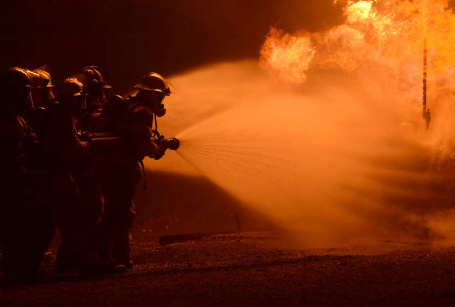 Midland Fire Department trainees approach a tank fire in a fog pattern during a controlled burn practice at the Harris Field Fire Training facility. James Durbin/Reporter-Telegram Photo: James Durbin