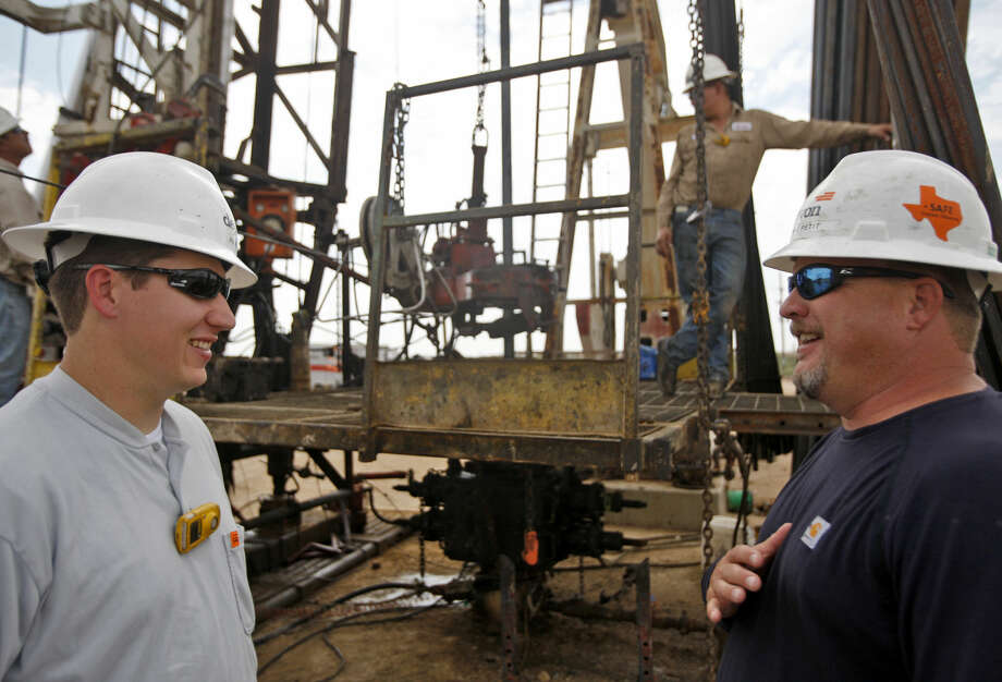 Joe Pfeil (left), an engineer with Devon Energy, on an active pumping rig located on Highway 385 south of Odessa, photographed Tuesday, Sept. 24, 2014. James Durbin/Reporter-Telegram Photo: James Durbin