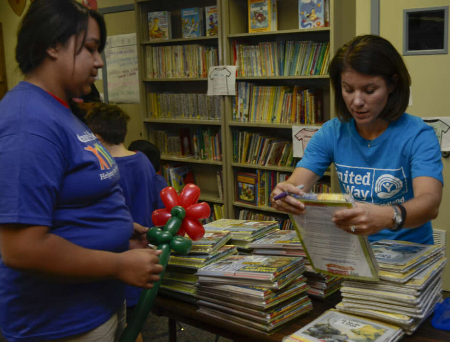 Alison King with United Way helps Vilma Renteria pick out her books Monday during the kickoff at Casa de Amigos of the summer reading program Club Read. Children at Casa all received their own books to read at Casa and take home to keep at the end of the summer. Tim Fischer\Reporter-Telegram Photo: Tim Fischer