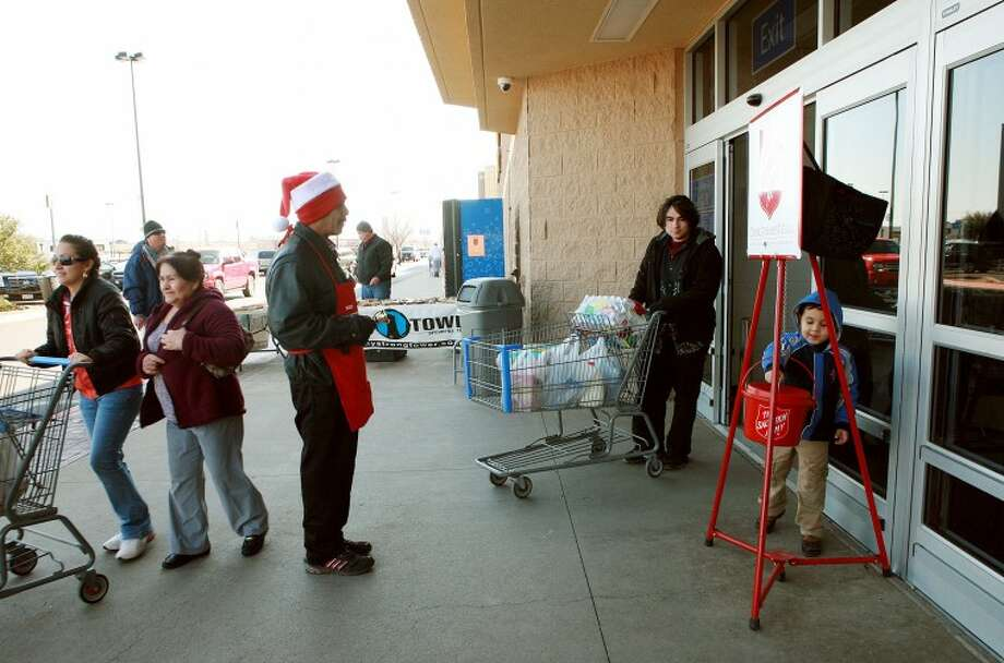 Salvation Army bell ringer Mario Martinez watches as Aiden Samaniego, 5, drops money into the collection pot Thursday at Walmart. Photo: Cindeka Nealy/Reporter-Telegram