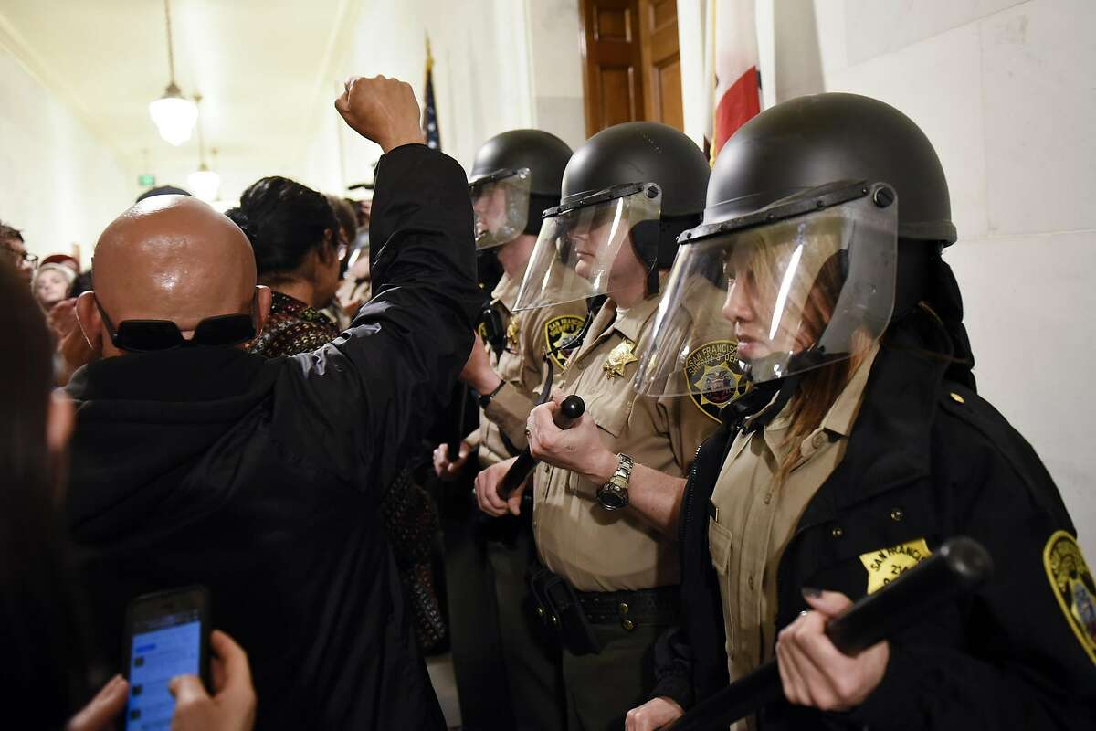 """A protester holds up his fist as he joins others supporting the """"Frisco Five"""" hunger strikers clash with police officers in front of the mayors office at City Hall in San Francisco in San Francisco, CA, Friday, May 6, 2016."""