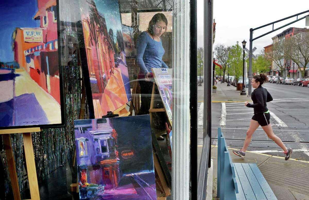 Amy Lavine, left, arranges paintings by New York artist Roger Mason in the window of her art supply and stationary shop, Sketch, on Warren Street Tuesday May 3, 2016 in Hudson , NY. (John Carl D'Annibale / Times Union)