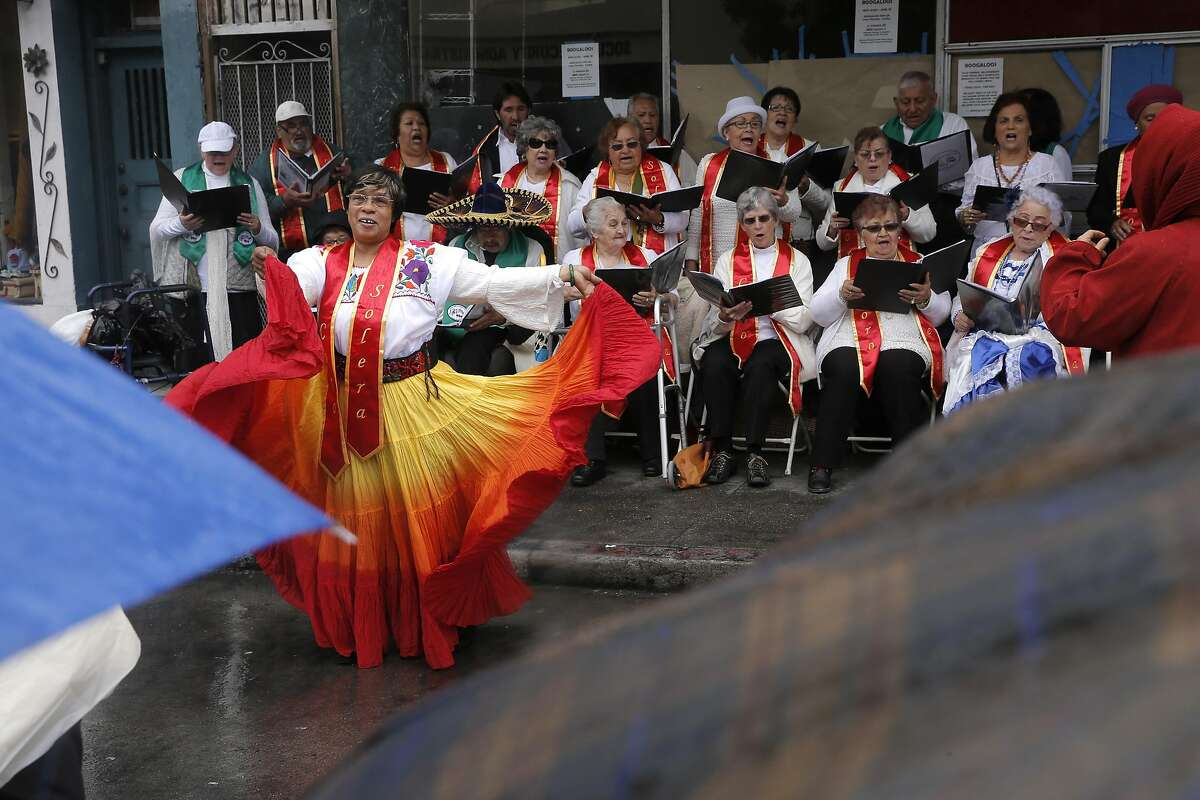 Christina Haynes dances with the adult choir from the Community Music Center of the Mission as they perform during the the Cinco de Mayo Festival on Saturday, May 7, 2016.