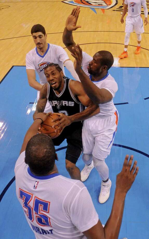 San Antonio Spurs' Kawhi Leonard looks for room between Oklahoma City Thunder's Kevin Durant (front to back), Serge Ibaka, and Enes Kanter during Game 3 in the Western Conference semifinals Friday May 6, 2016 at Chesapeake Energy Arena in Oklahoma City, Oklahoma. The Spurs won 100-96. Photo: Edward A. Ornelas, Staff / San Antonio Express-News / © 2016 San Antonio Express-News