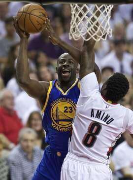 Golden State Warriors forward Draymond Green, left, shoots over Portland Trail Blazers forward Al-Farouq Aminu, right, during the first half of Game 3 of an NBA basketball second-round playoff series Saturday, May 7, 2016, in Portland, Ore. (AP Photo/Craig Mitchelldyer)