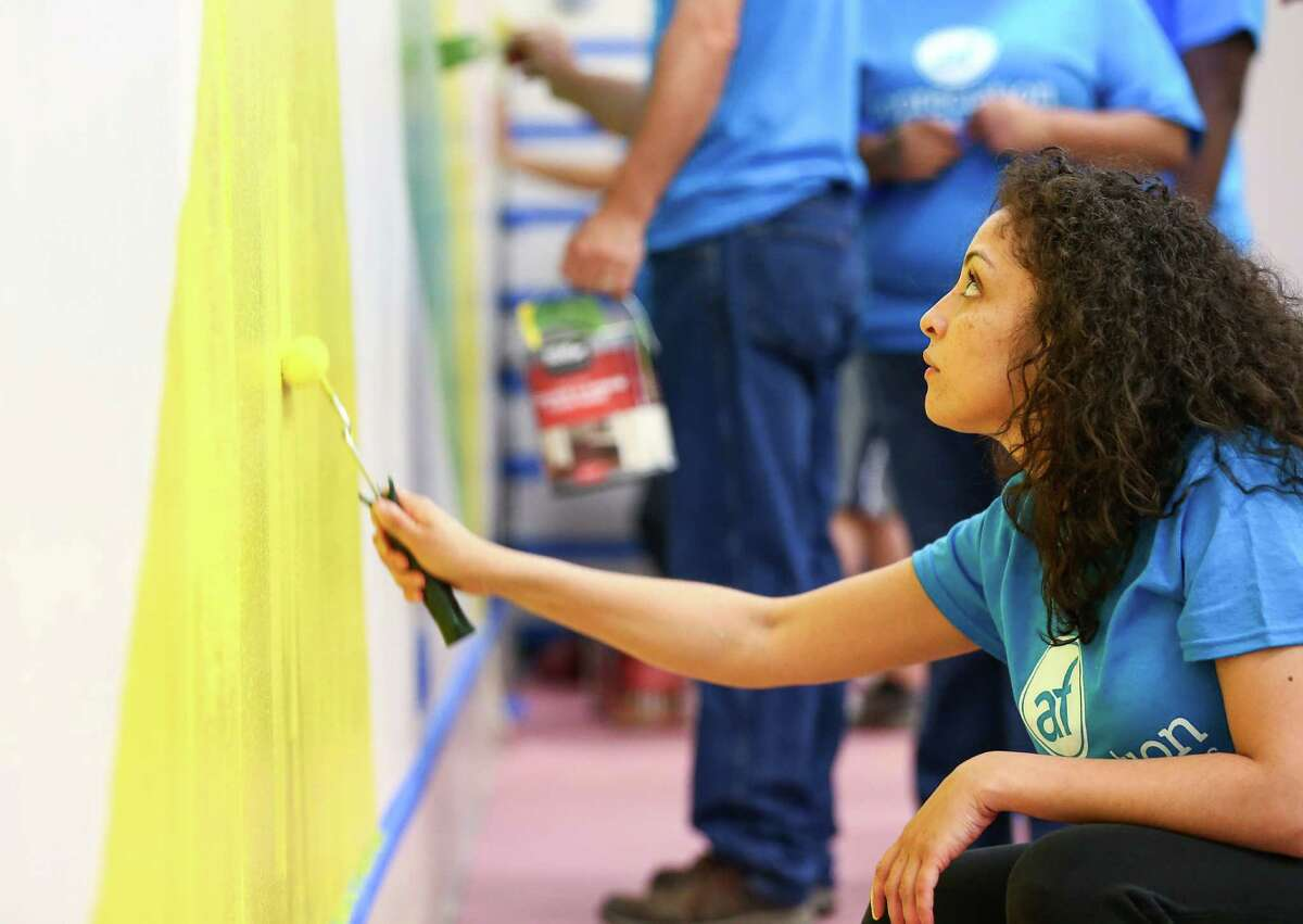 Michelle Madera helps other volunteers paint a cafeteria wall at the Houston Academy for International Studies, Saturday, May 7, 2016, in Houston. The campus was recently vandalized, and several dozen volunteers spent most of the day working on beautification projects.