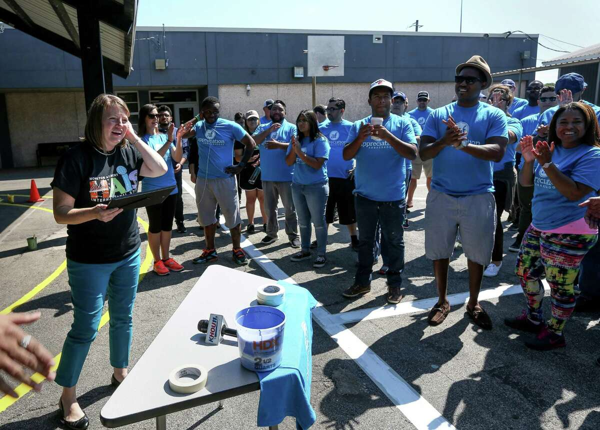 Melissa Jacobs-Thibeaut, principal of the Houston Academy for International Studies, reacts after receiving a $2,500 scholarship from Appreciation Financial Saturday, May 7, 2016, in Houston. Volunteers helped paint and beautiful the recently-vandalized campus.