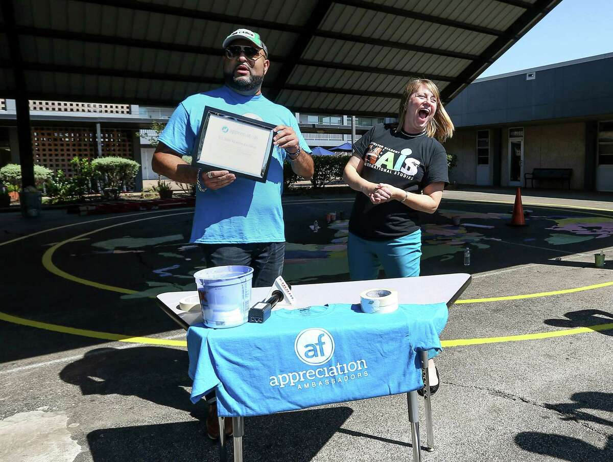Melissa Jacobs-Thibeaut, principal of the Houston Academy for International Studies, reacts after receiving a $2,500 scholarship from Dominique Moore, of Appreciation Financial, Saturday, May 7, 2016, in Houston. Volunteers helped paint and beautiful the recently-vandalized campus.