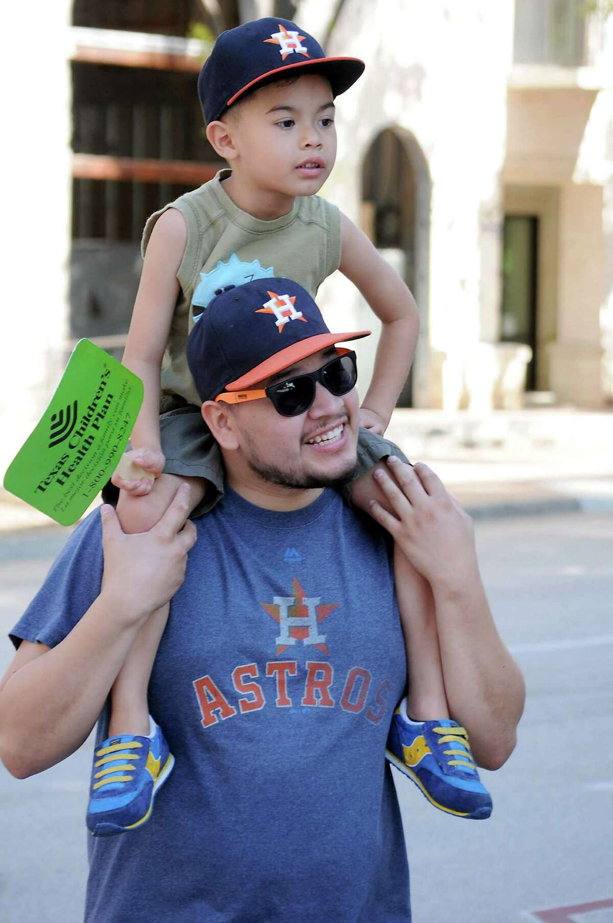 Bryan Flores and his son Bryan Jr watch the 21st Annual LULAC Cinco de Mayo Parade downtown Saturday May 7, 2016.