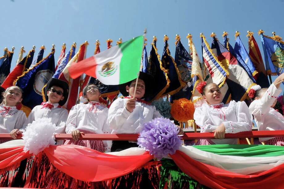 Children in costume wave flags aboard the E.A. Squatty Lyons float in the 21st Annual LULAC Cinco de Mayo Parade downtown Saturday  May 7, 2016. Photo: Dave Rossman, For The Chronicle / Dave Rossman