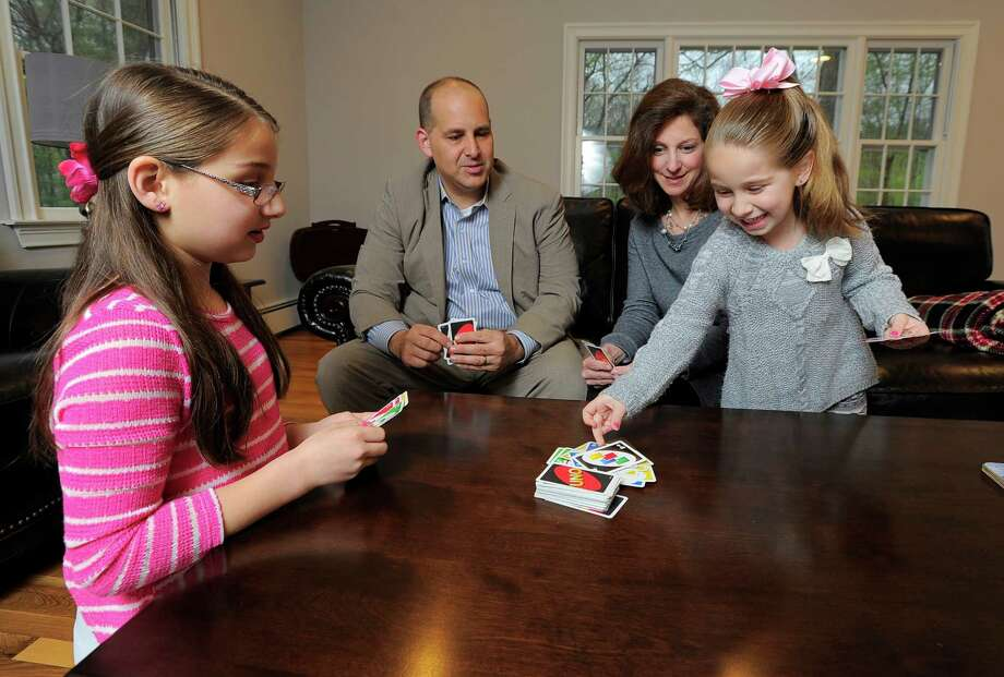 The LaMagna family, from left, Julianna, 10, Michael, Nina and Gabriella, 6, play a card game of Uno on May 6, 2016 at their home in Stamford. The family moved into a quiet North Stamford neighborhood a year ago from Norwalk. Photo: Matthew Brown / Hearst Connecticut Media / Stamford Advocate