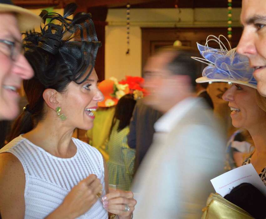 Amid flower and Derby Day finery, Samantha Collin, left, meets her friend Alicia Westerlund at the Pequot Library party.
