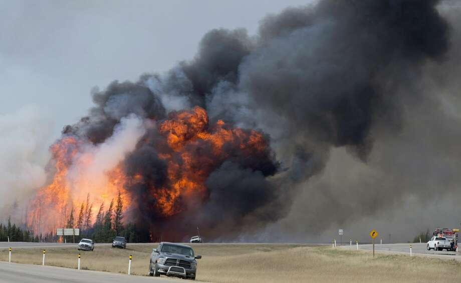 A wildfire burns south of Fort McMurray, Alberta, near Highway 63 on Saturday, May 7, 2016. Canadian officials hoped to complete the mass evacuation of work camps north of Alberta's main oil sands city of Fort McMurray on Saturday, fearing the growing wildfire could double in size and reach a major oil sands mine and even the neighboring province of Saskatchewan.  (Jonathan Hayward /The Canadian Press via AP) MANDATORY CREDIT Photo: AP