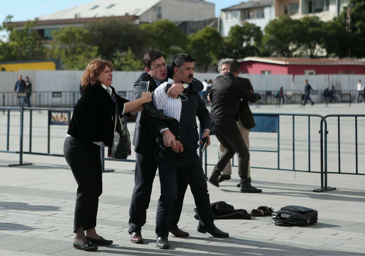 Dilek Dundar, left, the wife of journalist Can Dundar, and his lawyer, second left, overpower a gunman just after the attack on Can Dundar, protected by a man in the rear, outside city's main courthouse in Istanbul, Friday, May 6, 2016. A man shouted ?