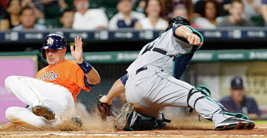 Houston Astros catcher Jason Castro left, slides past Seattle Mariners catcher Chris Iannetta right, to score a run during the fifth inning of MLB game action at Minute Maid Park Friday, May 6, 2016, in Houston. Photo: James Nielsen, Houston Chronicle / © 2016  Houston Chronicle